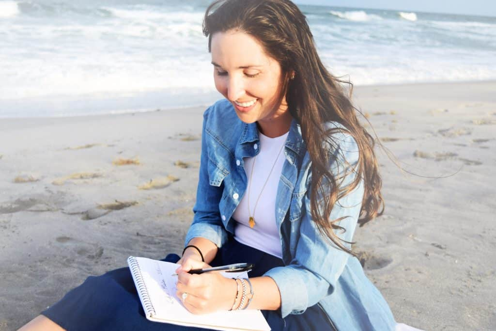 millennial blogger journaling on beach, importance of nature and mental health